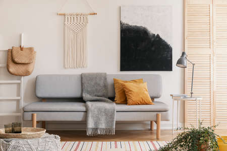 Abstract black and white painting and handmade macrame on white wall of natural living room interior with grey fashionable couch with yellow pillow and warm blanket