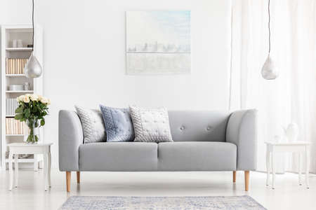 Flowers on table next to grey settee with pillows in apartment interior with poster and lamps. Real photo Stock Photo