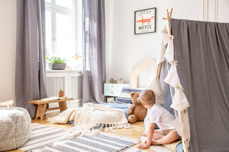 Patterned carpet on parquet of cozy boys bedroom with comfortable bed and scandinavian tent, real photo with copy space