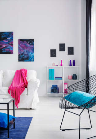 Blue pillow on black stylish metal armchair in bright cosmos inspired interior with white furniture, real photo with copy space on the wall