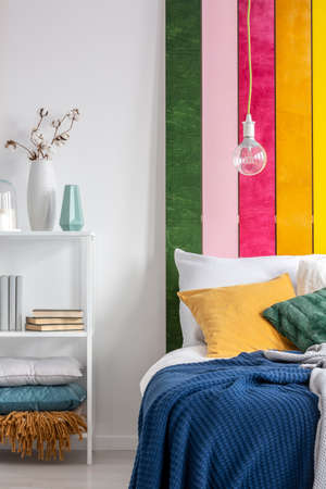 Real photo of a bare light-bulb hanging above a white bed with yellow pillow and blue blanket in folk bedroom interior