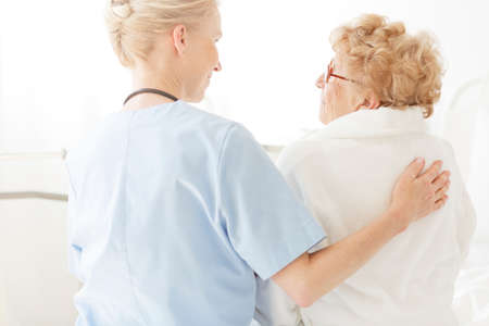 Helpful nurse sitting on a hospital bed next to an older woman and strokes her back