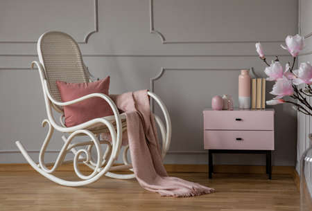 Pink blanket on rocking chair in grey living room interior with flowers and cabinet. Real photo Standard-Bild - 118386562