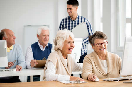 Young handsome teacher and group of active seniors during computer classes for elderly Stock Photo