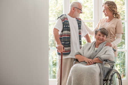 Senior woman in wheelchair visited by her husband and nurse