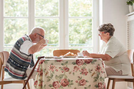 Elder husband and wife having a tea and cake together at the table