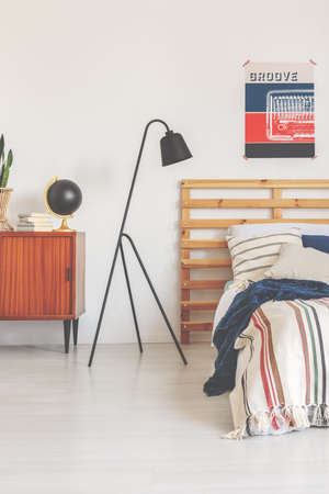Real photo of a modern lamp in a retro bedroom interior with a bed, poster and wooden cupboard Stok Fotoğraf