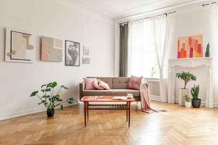 Wooden table in front of sofa with pink blanket in apartment interior with posters and plants. Real photo