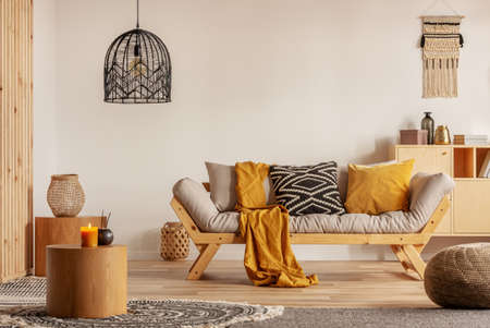 Scandinavian sofa with pillows and dark yellow blanket in bright living room interior with black chandelier Stok Fotoğraf - 118480869