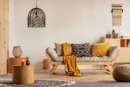 Skandinavisches Sofa mit Kissen und dunkelgelber Decke im hellen Wohnzimmer mit schwarzem Kronleuchter Standard-Bild