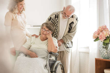 Paralysed wife and her husband smiling in a nursing home assisted by a nurse