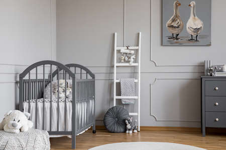 Plush toy on pouf in front of grey bed in child's bedroom interior with ladder and poster. Real photo