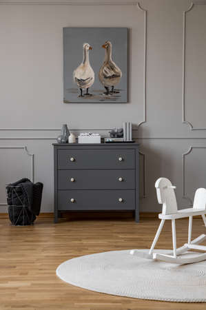 Poster above grey cabinet in kid's room interior with rocking horse on round rug. Real photo Standard-Bild