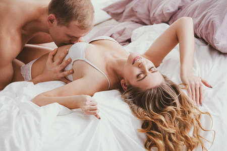 Smiling woman wearing underwear and man kissing her during sensual foreplay Stock Photo