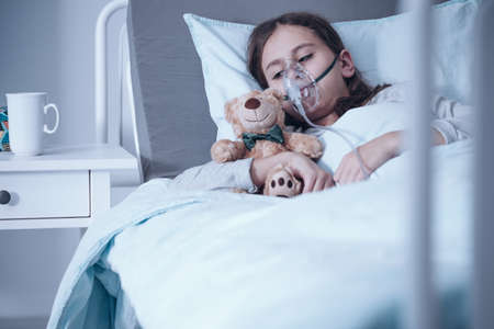 Sad kid with cystic fibrosis lying in a hospital bed with oxygen mask and plush toy Stock Photo