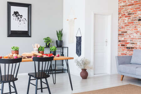 Real photo of an industrial dining room interior with a table, food on it, plants, black chairs and brick wall next to a door
