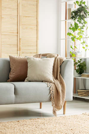 Pastel pillows on a sofa in a cozy living room interior. Real photo