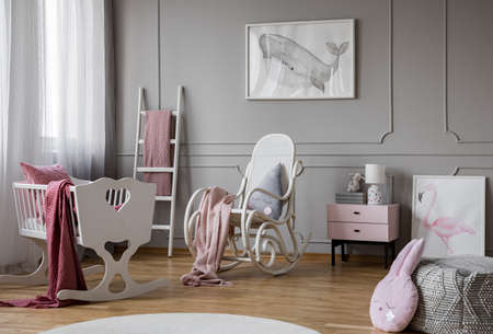 White cradle next to rocking chair in grey babys bedroom interior with whale poster. Real photo