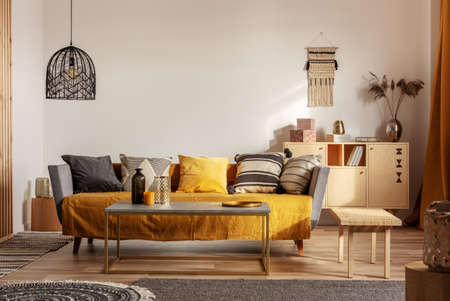 Fashionable living room interior with yellow and grey design and long coffee table in the middle