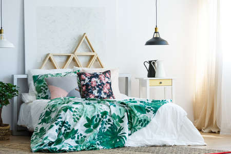 Floral bedding on cozy king size bed in classy bedroom with silver painting and wooden triangles as headboard