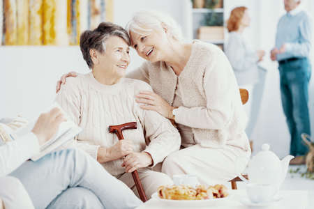 Two smiling senior best friends spending time together at school reunion Stock Photo