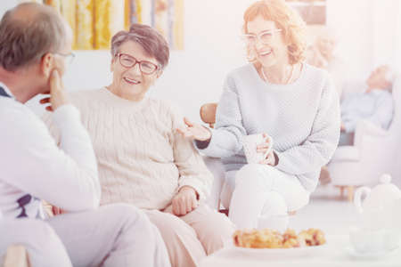 Happy group of elderly people talking and enjoying each others company at Senior club Stock Photo