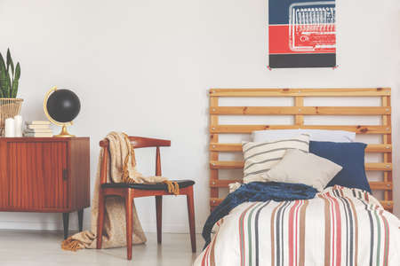Real photo of a teenager room interior with a bed, pillows, a wooden chair and poster
