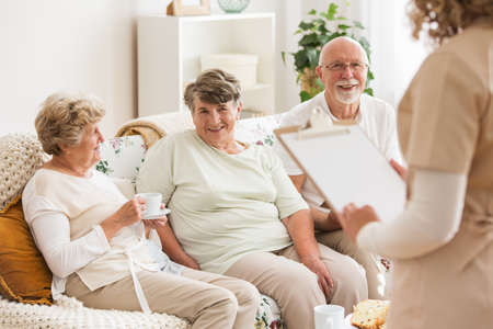 Happy elders sitting on a couch while talking to a nurse Stock Photo