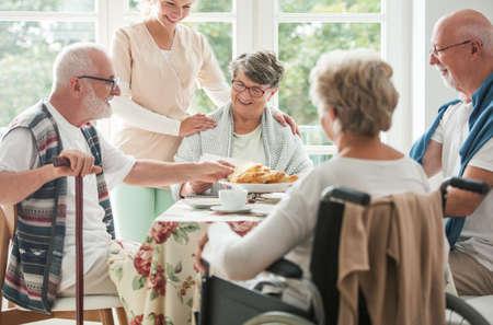 Happy seniors having a cake in a nursing home