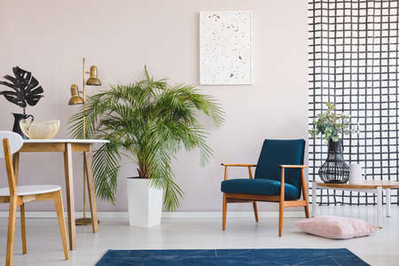 Chair at wooden table in bright dining room interior with plants and poster above armchair. Real photo