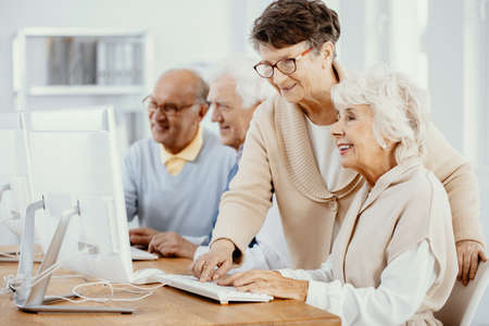 Senior women making project at computer class for elderly people
