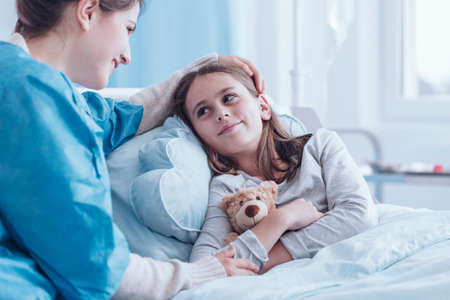 Smiling caregiver visiting happy, sick girl in the health center Stock Photo