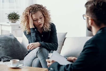 Blondynka przytłoczona bizneswoman siedząca na kanapie w gabinecie psychoterapeuty Zdjęcie Seryjne