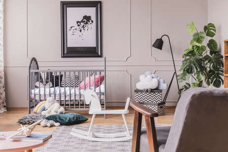 Rocking horse and toys in front of bed in babys bedroom interior with poster and lamp. Real photo