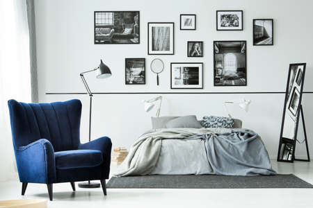 Comfortable blue armchair in monochromatic bedroom interior with king size bed and gallery of posters on the wall