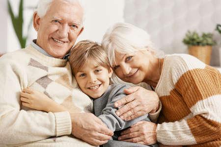 Abuelos felices abrazando a su nieto