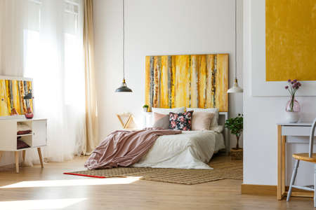 Floral pillow and pastel pink bedding on king size bed in chick bedroom interior with abstract painting on the wall and checkered carpet on wooden floor Stock Photo