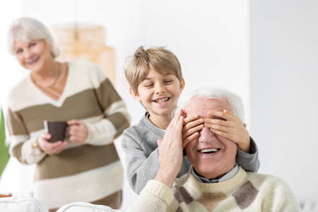 Smiling grandson covering his grandfathers eyes while grandmother is looking at them Stock Photo