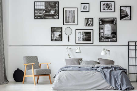 Elegant retro armchair next to king size bed with grey bedding in contemporary bedroom interior with black and white photos