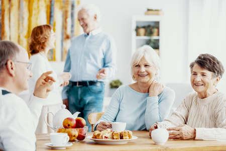 Happy senior people enjoying their meeting, talking and sharing memories while drinking tea at nursing home