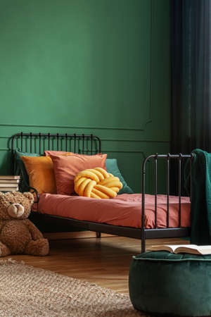Knot yellow pillow on single metal bed with dark orange bedding, copy space on empty dark green wall