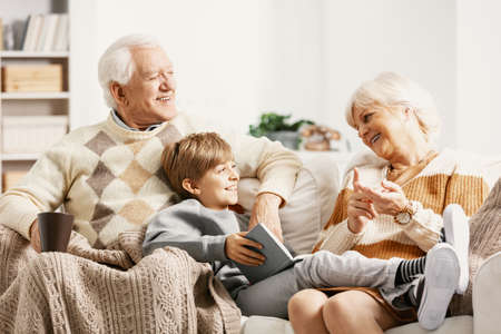 Grandson talking to his grandmother while lying on the laps of his grandfather Stock Photo