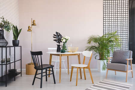 Chair at wooden table with flowers in dining room interior with armchair and gold lamp. Real photo