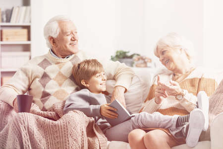 Grandparents spending good time with their grandson on a couch and reading a book Standard-Bild - 118448930