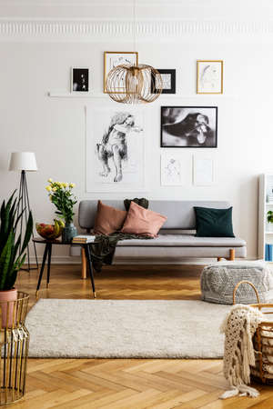 Posters above grey couch with pillows next to table with flowers in living room interior. Real photo