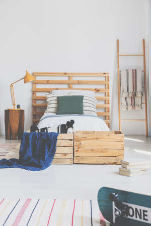 Real photo of a bedroom interior with a bed and pallet as a headrest Stock Photo