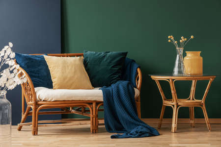 Yellow, emerald green and blue pillows on rattan, copy space on the empty green and blue wall Stock fotó