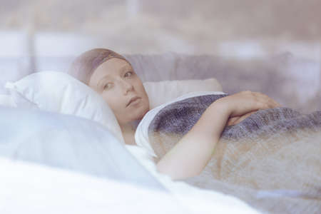 Thoughtful woman battling with tumor lying in hospice bed