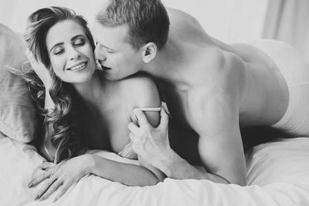 Man kissing smiling woman during romantic sex. Couple embracing in the bedroom Stock Photo
