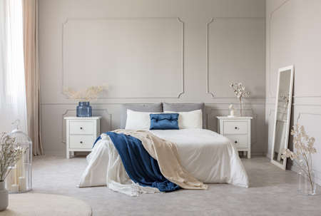 King size bed with grey, blue and white bedding between two wooden nightstands with flowers in vases, copy space on empty grey wall